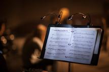lights on a music stand illuminating sheet music