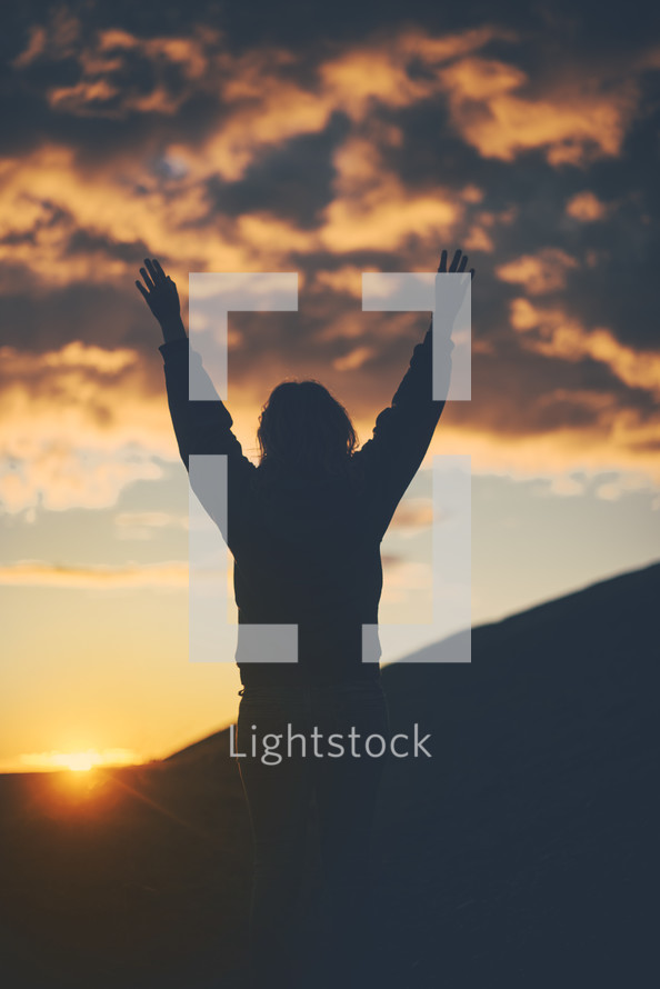 silhouette of woman with raised hands at sunset