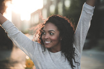a young African-American woman outdoors under intense sunlight with hands in the air