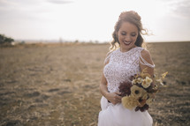 a bride holding a bouquet of fall flowers