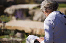 an elderly woman reading a Bible in her lap outdoors