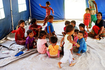 refugee children sitting on the floor in a tent classroom