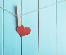 Clothespin holds red paper heart against a blue wall.