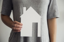 man holding a paper cutout of a house