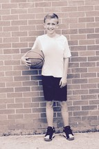 a boy holding a basketball standing against brick wall