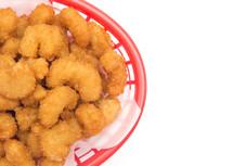 Battered and Fried Popcorn Shrimp in a Basket on a White Background