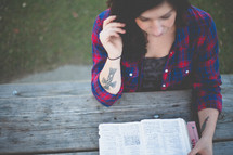 Woman reading the Bible at an outdoor picnic table.