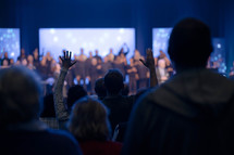 raised hands in the audience at a worship service