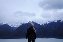 a woman in a coat looking out at mountains and lake view
