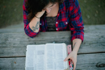 Woman reading the Bible while sitting at a picnic table outside.