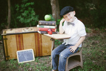 portrait of a boy child sitting in a desk with apples