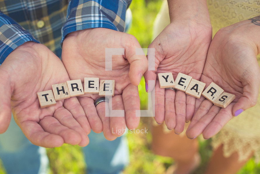 """A man and woman's hands holding game pieces spelling """"three"""" and """"years."""""""