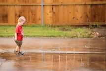 a toddler boy splashing in puddles