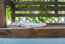 a BIble on a porch swing