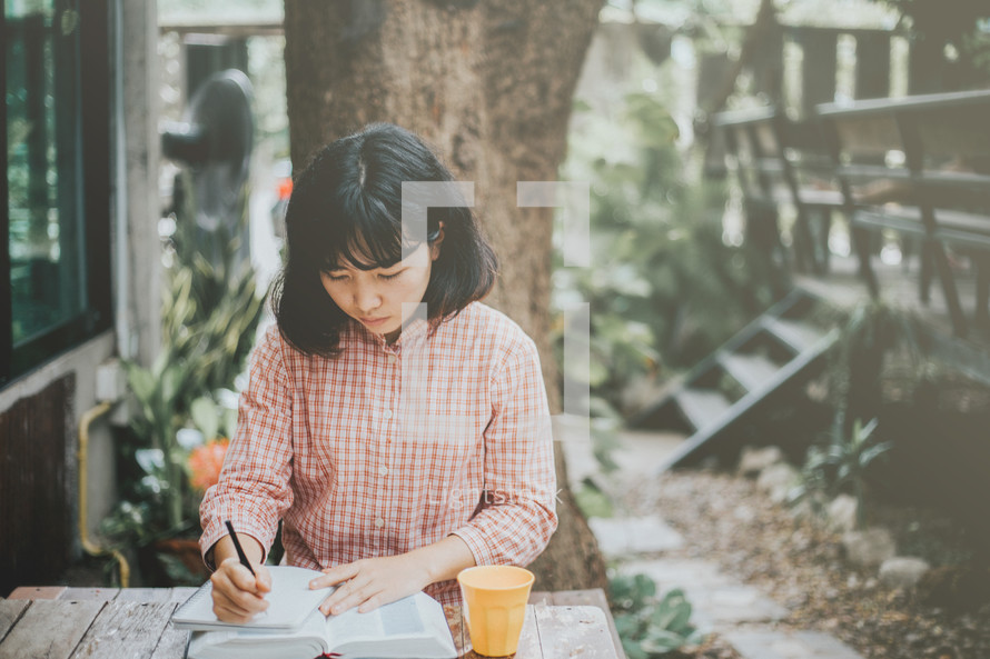 a woman sitting at a table outdoors reading a Bible and writing in a journal