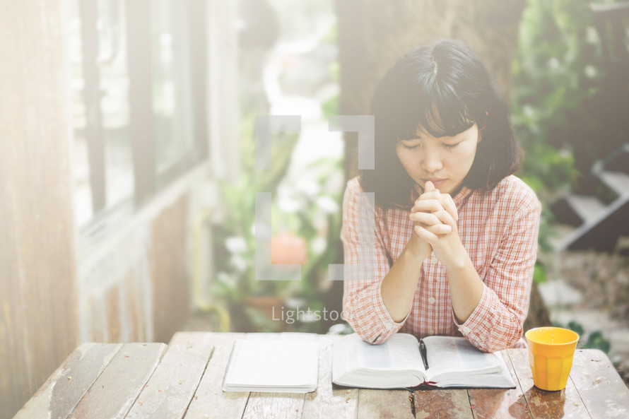 a woman praying sitting at a table with an open Bible