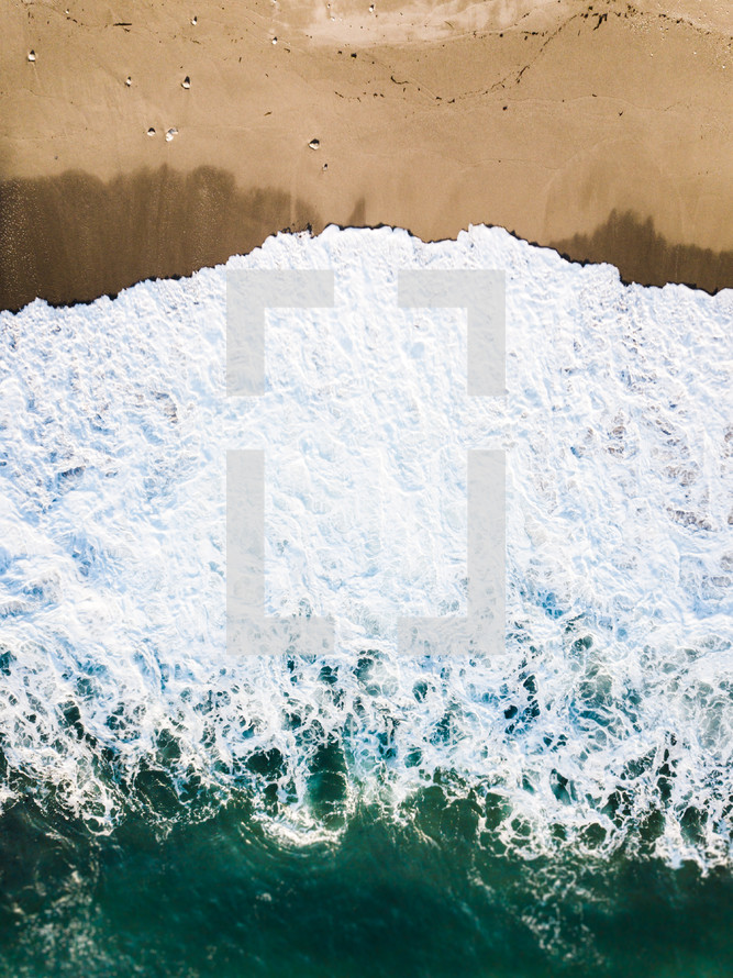 aerial view over a tide washing onto a beach