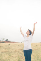 Woman standing in a field with arms raised in praise.