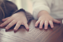 Children's hands on a wooden table.