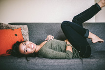 Young woman laing down on a couch, kicking legs up