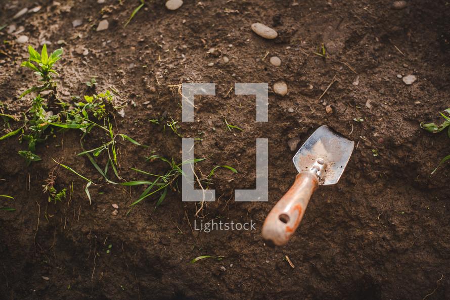 handheld shovel in dirt
