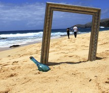 Couple holding hands while walking on the beach, seen through a frame near a glass bottle.