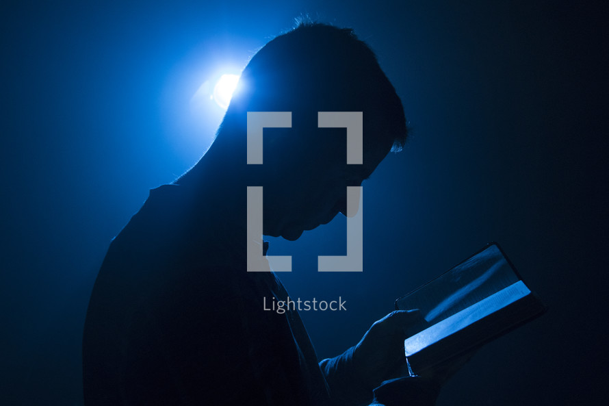 Man holding Bible with light from behind and blue tones