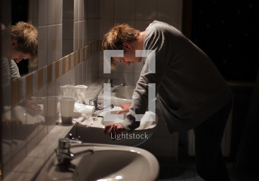 Man leaning over a sink in a bathroom.
