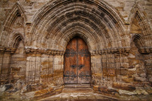 Ornate wooden doorway in the stone arch of an ancient cathedral.