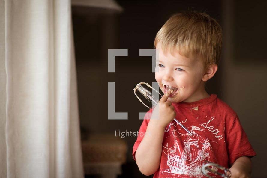 a little boy licking batter from a mixer