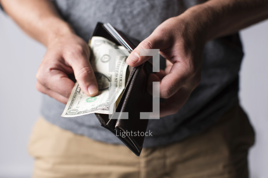 man pulling a dollar out of his wallet