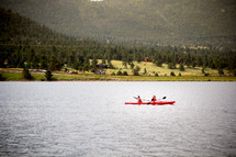 paddling in kayaks on a lake in summer