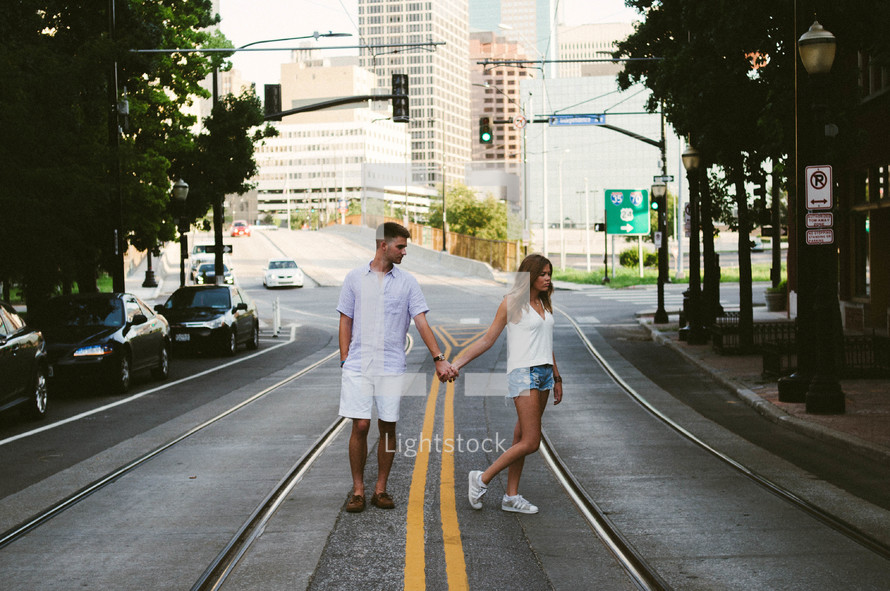 A young man and woman holding hands and walking together down a city street.