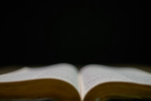 Open bible up close against a black background
