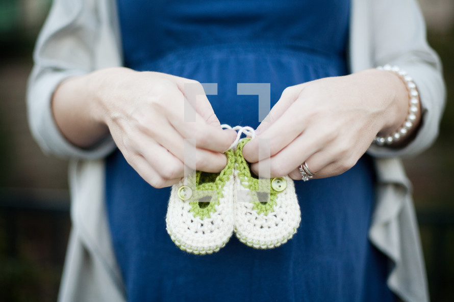 a pregnant mother holding knitted booties