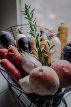 fresh picked carrots, potatoes, and onions in a basket