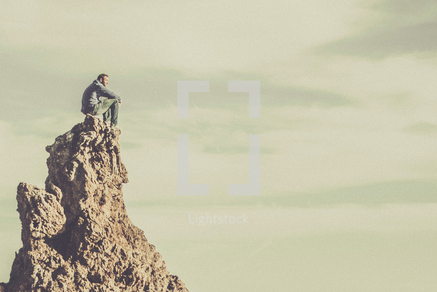 A man sitting on a rock formation.