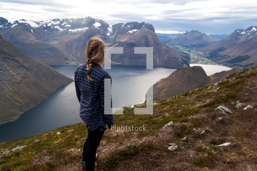 a woman looking out at the view standing at the top of mountain
