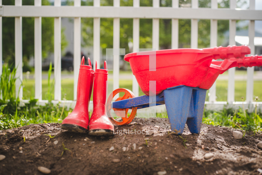 red rain boots and toy wheelbarrow