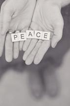 word peace in scrabbles pieces in a woman's hands
