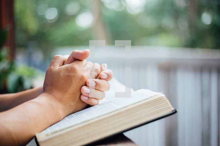 praying hands over pages of a Bible