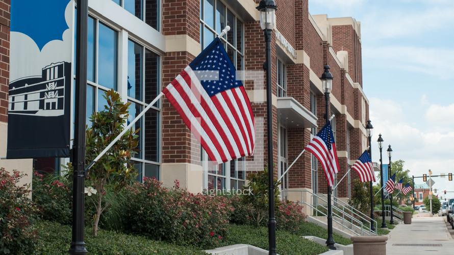 row of American flags on flag poles along a sidewalk