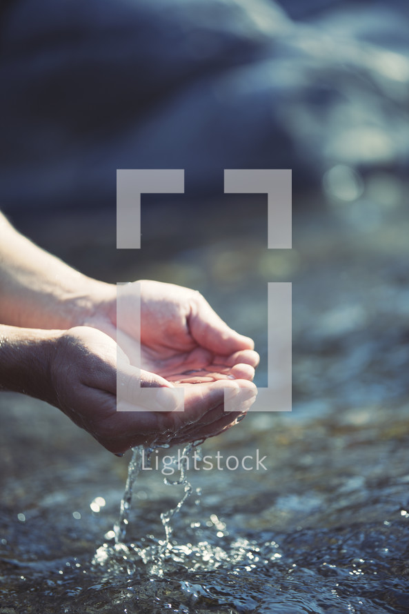 cupped hands gathering water from a stream