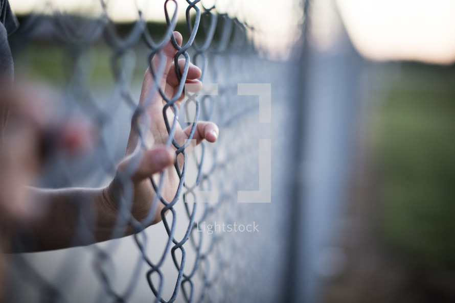 A hand gripping a chain link fence.