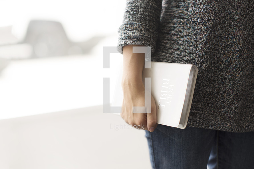 a woman holding a Bible at her side