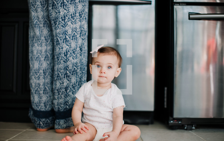 an infant girl sitting on the kitchen floor next to mom
