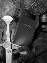 suit of armor with a sword and Bible.