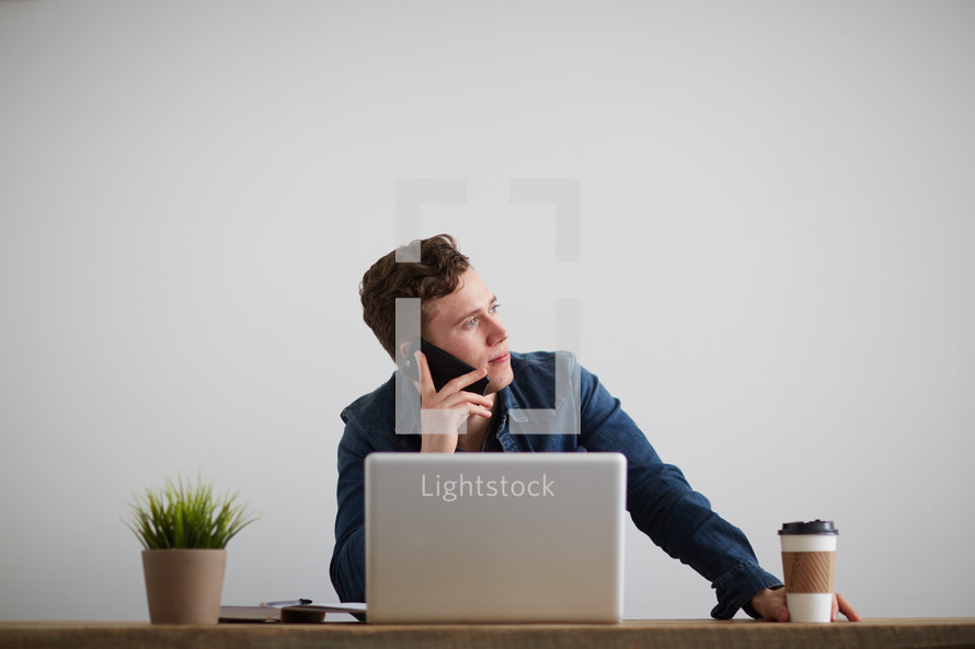 a man sitting behind a computer talking on a cellphone