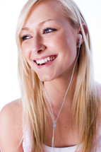 a young woman smiling while listening to music