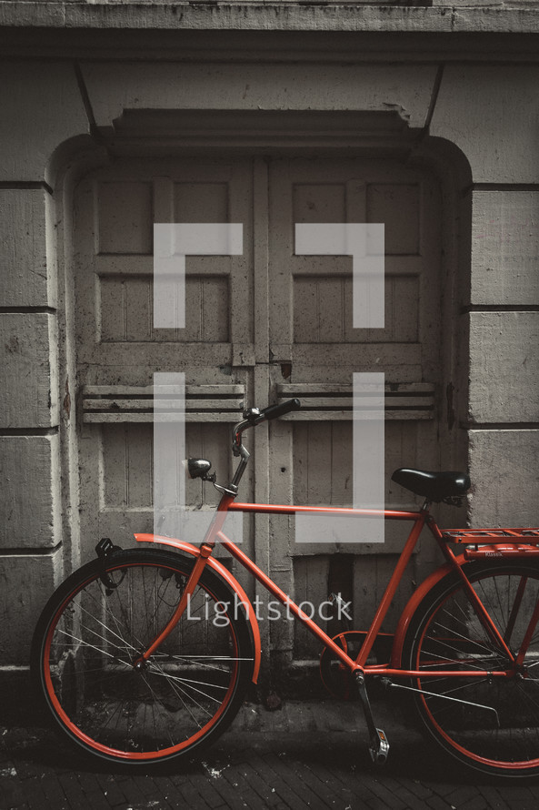 red bicycle parked in front of gray doors